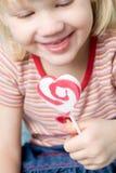 Petite fille avec une lucette de forme de coeur Photo stock