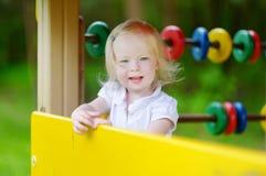 Petite fille ayant l'amusement à un terrain de jeu Photos stock