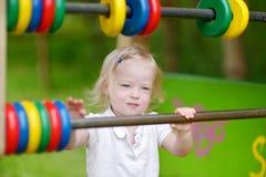 Petite fille ayant l'amusement à un terrain de jeu Image libre de droits