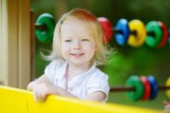 Petite fille ayant l'amusement à un terrain de jeu Images libres de droits