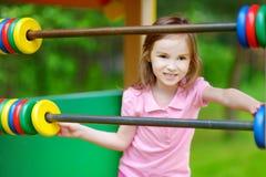 Petite fille ayant l'amusement à un terrain de jeu Photographie stock