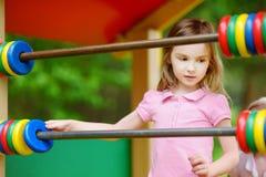 Petite fille ayant l'amusement à un terrain de jeu Images stock