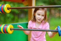 Petite fille ayant l'amusement à un terrain de jeu Photographie stock libre de droits
