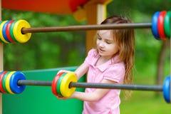 Petite fille ayant l'amusement à un terrain de jeu Photo libre de droits
