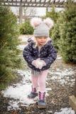 Petite fille ayant l'amusement jouant avec la neige tout en sélectionnant un chr photo stock