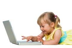 Petite fille ayant l'amusement sur l'ordinateur portable. photo libre de droits