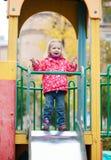 Petite fille ayant l'amusement sur la cour de jeu Photos libres de droits