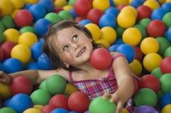 Petite fille ayant le temps d'amusement dans le regroupement de billes photos stock