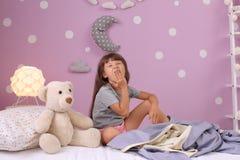 Petite fille baîllant sur le lit à la maison photos stock