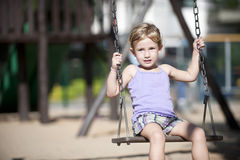 Petite fille balançant sur la cour de jeu Photos stock
