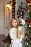 Petite fille blonde adorable avec des yeux bleus souriant, et tenant a images libres de droits