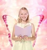 Petite fille blonde affichant un livre - imagination Image libre de droits