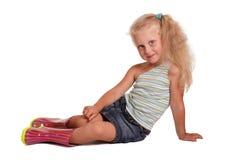 Petite fille blonde avec du charme assise en chemisier, jupe et caoutchouc BO images libres de droits