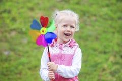 Petite fille blonde bouclée riante tenant le soleil multicolore Images libres de droits