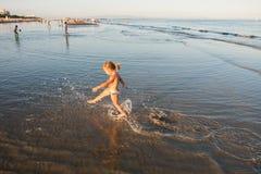 Petite fille blonde caucasienne courant sur le sable de plage au coucher du soleil photographie stock