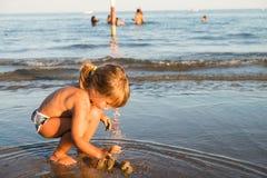 Petite fille blonde caucasienne jouant avec le sable photos stock