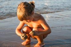 Petite fille blonde caucasienne jouant avec le sable photographie stock libre de droits