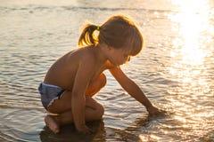Petite fille blonde caucasienne jouant avec le sable photographie stock