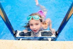Petite fille blonde dans la piscine avec des lunettes photos libres de droits