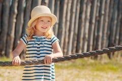 Petite fille blonde dans le chapeau et la robe barrée Image stock