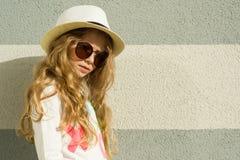 Petite fille blonde de portrait extérieur avec les longs cheveux bouclés, lunettes de soleil dans le chapeau de paille Fond textu images libres de droits
