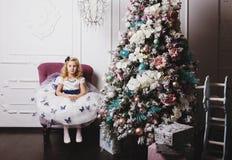 Petite fille blonde en cadeaux de attente de belle robe se reposant près de l'arbre de Noël à la maison Photo libre de droits
