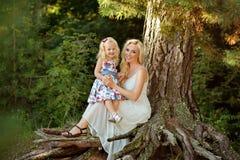 Petite fille blonde et son se reposer de sourire de maman sur un arbre dans Photos libres de droits