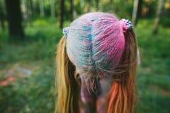 Petite fille blonde jouant avec la peinture sèche et les sourires Images stock