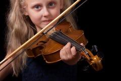 Petite fille blonde jouant le violon d'isolement sur un fond noir images libres de droits