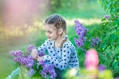 Petite fille blonde mignonne de sourire d'enfant 4-9 ans avec un bouquet de lilas dans les mains dans les jeans et la chemise Images libres de droits