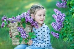 Petite fille blonde mignonne de sourire d'enfant 4-9 ans avec un bouquet de lilas dans les mains dans les jeans et la chemise Photographie stock