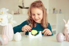 Petite fille blonde mignonne peignant des oeufs de pâques images stock