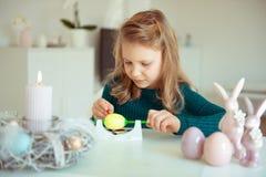 Petite fille blonde mignonne peignant des oeufs de pâques photo stock