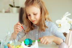 Petite fille blonde mignonne peignant des oeufs de pâques images libres de droits