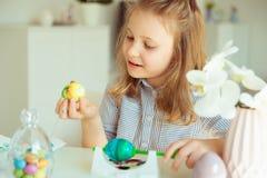 Petite fille blonde mignonne peignant des oeufs de pâques photos stock