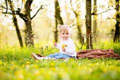Petite fille blonde mignonne s'asseyant sur une couverture dans une herbe dans orchar Images stock