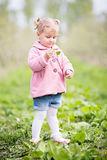 Petite fille blonde mignonne se tenant dans le verger et tenant une pomme t Images stock