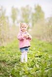 Petite fille blonde mignonne se tenant dans le verger et tenant une pomme t Images libres de droits