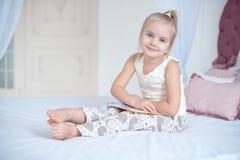 Petite fille blonde mignonne se trouvant sur le lit image stock