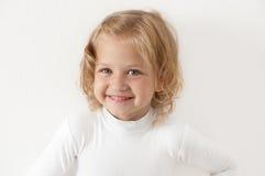 Petite fille blonde rectifiée dans le blanc Photographie stock