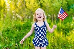 Petite fille blonde riante avec de longs cheveux tenant le drapeau américain Images libres de droits