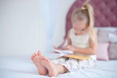 Petite fille blonde s'asseyant sur le lit lisant un livre photos libres de droits