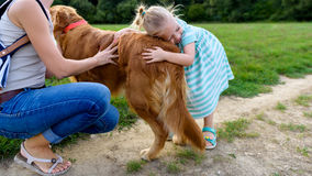 Petite fille blonde souriant et étreignant son golden retriever mignon de chien Photo libre de droits