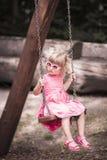 Petite fille blonde sur une oscillation Photographie stock