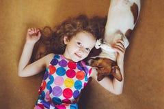 Petite fille bouclée étreignant un chiot Images stock