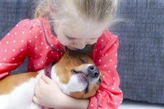 Petite fille bouclée blonde étreignant un chien de basenji Photographie stock