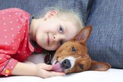 Petite fille bouclée blonde étreignant un chien rouge de basenji Image libre de droits