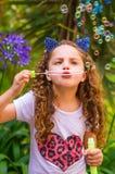 Petite fille bouclée heureuse jouant avec des bulles de savon sur une nature d'été, port oreilles bleues des accessoires de tigre Photos libres de droits