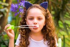 Petite fille bouclée heureuse jouant avec des bulles de savon sur une nature d'été, port oreilles bleues des accessoires de tigre Image stock