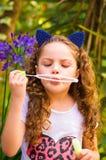 Petite fille bouclée heureuse jouant avec des bulles de savon sur une nature d'été, port oreilles bleues des accessoires de tigre Photographie stock libre de droits